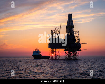 A oil platform in the North sea with a supply vessel alongside during sunset. - Stock Photo