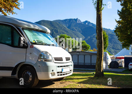RV standing on a campsite in Ticino / Switzerland with view towards Alps - Stock Photo