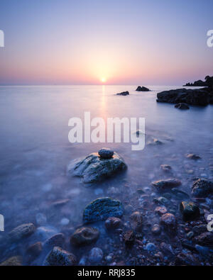 A colourful spring sunrise over Torbay with warm light glinting off the wet rocks, Anstey's Cove, Torquay, Devon, England, United Kingdom, Europe - Stock Photo