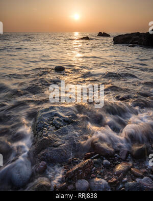 A colourful sunrise over Torbay with warm light glinting off the wave and wet rocks, Anstey's Cove, Torquay, Devon, England, United Kingdom, Europe - Stock Photo