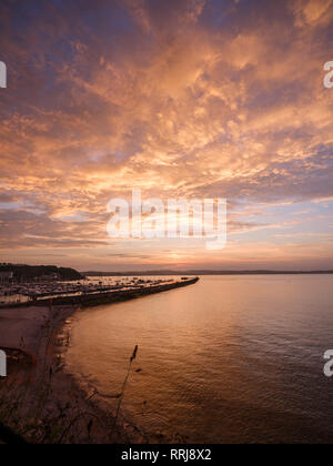 Colourful sunset view of Breakwater Beach and the harbour wall of Brixham, Devon, England, United Kingdom, Europe - Stock Photo