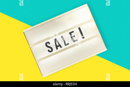 Light box with sale letters on yellow and blue backdrop - Stock Photo
