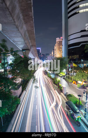 View of elevated skytrain track and traffic light trails on Sukhumvit Road in downtown Bangkok, Thailand, Southeast Asia, Asia - Stock Photo