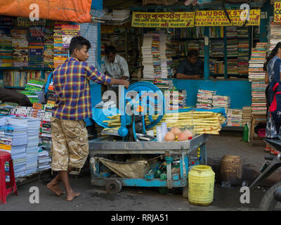 Man with sugarcane mill in front of stationery shop, Kolkata, West Bengal, India - Stock Photo