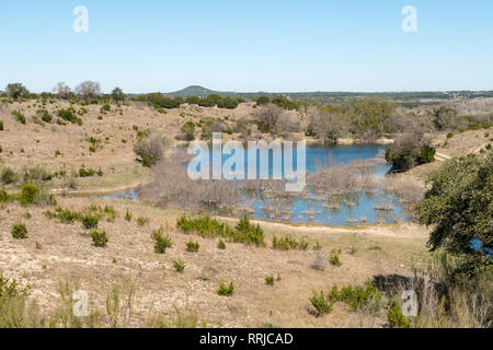 View of Large Rock Formation in the Distance With Lake in the Foreground - Stock Photo