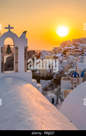 View of traditional blue domed churches and white houses at sunset in Oia, Santorini, Cyclades, Aegean Islands, Greek Islands, Greece, Europe - Stock Photo