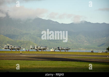A-10 Thunderbolt II attack aircraft assigned to the 442d Fighter Wing sit on the ramp as the sun rises over Kaneohe Bay Feb. 21, 2019, at Marine Corps Base Hawaii. The 442d conducted joint exercises with U.S. Marines, testing their capabilities alongside MV-22 Osprey tiltrotor aircraft. (U.S. Air Force Photo by Tech. Sgt. Bob Jennings) - Stock Photo