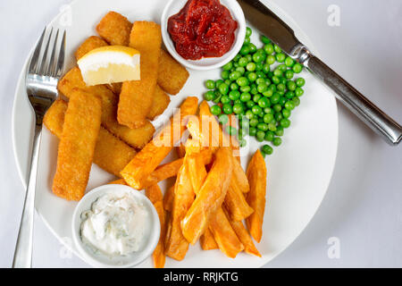 Classic English pub lunch of Fish fingers, chips and garden peas served with homemade Tomato ketchup, Tartar sauce and fresh Lemon wedge. - Stock Photo