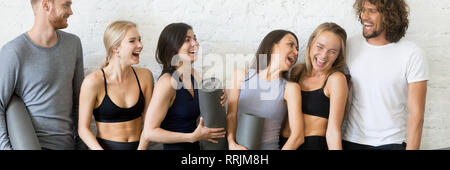 Laughing people resting after workout standing in row near wall - Stock Photo