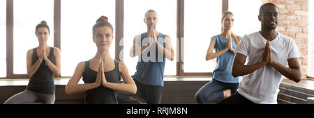 Horizontal image people during yoga session standing in Tree pose - Stock Photo