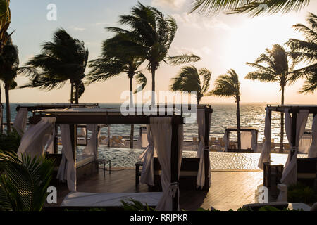 Private beds in a lounge area of a a high end Mexican resort overlooking the ocean at sunrise. - Stock Photo