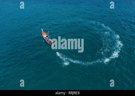 View from above, aerial view of a beautiful longtail boat sailing on a deep blue sea creating a circle shape with its wake, Phuket, Thailand. - Stock Photo