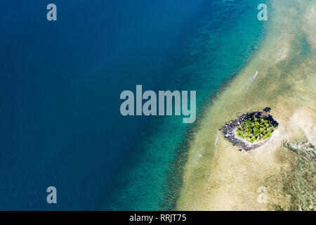 View from above, aerial view of a little island on a stunning barrier reef with beautiful shades of blue and turquoise sea. West coast of Phuket. - Stock Photo
