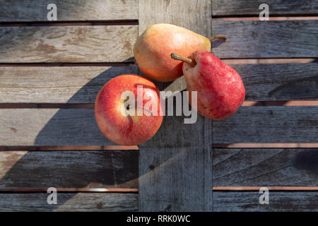 Two red and yellow pears and an apple lie on a rustic garden table in the sun. - Stock Photo