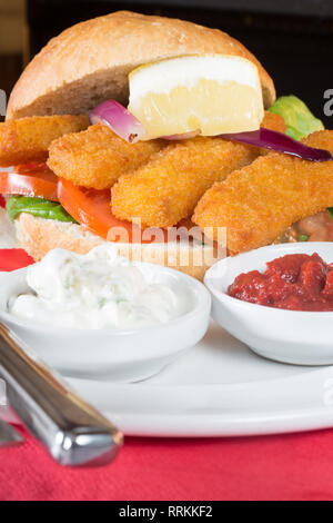 Typical English lunch snack of Fish fingers in a bun with ketchup and Tartar. - Stock Photo