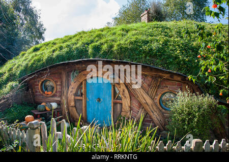 Hobbiton movie set, Matamata, New Zealand. . Quaint little Hobbit house with turquoise door,  in a green, sunny hillside landscape and blue sky - Stock Photo