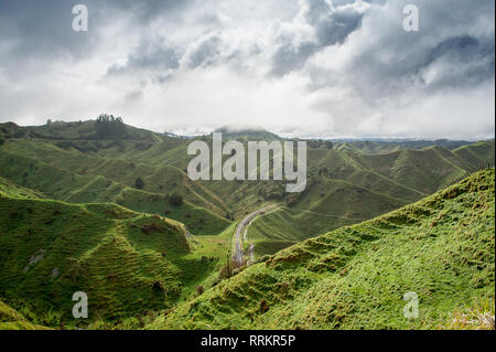The Tahora Saddle, part of The Forgotten World Highway, North Island, New Zealand. Pastoral landscape, green steep sided hills and dark stormclouds - Stock Photo