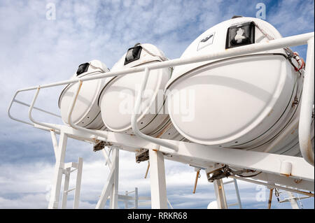 Life rafts on board a passenger ferry. Upwards view of three lifeboat capsules against a blue cloudy sky background - Stock Photo