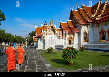Two Buddhist monks walking in the manicured grounds of Wat Benchamabophit (also known as Marble Temple), in Bangkok, Thailand - Stock Photo