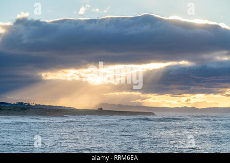 Clouds part during a sunrise along the California coast, creating stunning light rays through the ocean spray.