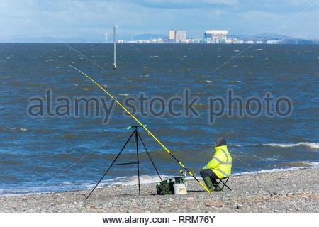 Fisherman on the beach in Fleetwood, Lancashire, England, UK with the Heysham Nuclear Power Station in the distance - Stock Photo
