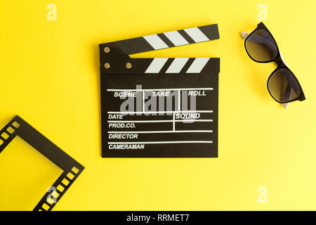 Flat lay of clapper board and glasses with film strip frame isolated on yellow. - Stock Photo