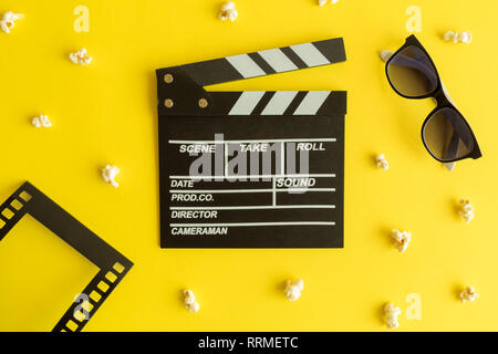 Flat lay of clapper board and glasses with film strip frame and popcorn isolated on yellow. - Stock Photo