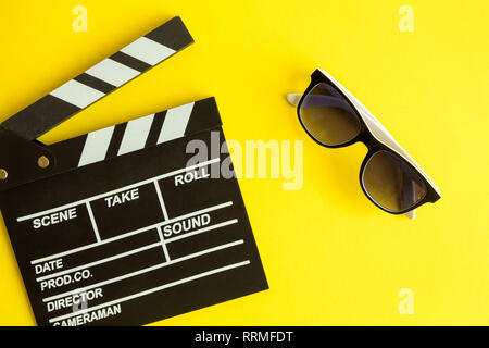 Cinema and movie making background. Clapperboard and 3d glasses isolated on yellow background minimal creative concept. - Stock Photo