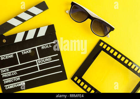 Cinema and movie making background. Clapperboard with 3d glasses and frame in form of film strip isolated on yellow background minimal creative concep - Stock Photo
