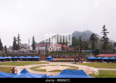 The outdoor market in large field by the Nhà Thờ Đá Sapa or Notre Dame cathedral on an overcast day, Sa Pa, Vietnam - Stock Photo