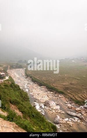 A river runs past terraced fields on a foggy day, Sa Pa, Vietnam - Stock Photo