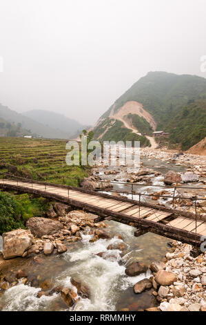 A wooden bridge over a river with hills in background on a foggy day, Sa Pa, Vietnam - Stock Photo