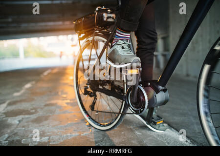 Midsection of unrecognizable businessman commuter with electric bicycle traveling from work in city. Copy space. - Stock Photo