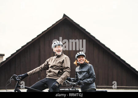 An active senior couple with helmets and electrobikes standing outdoors in front of a house. - Stock Photo
