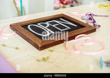 selective focus of wooden chalk board with 'open' lettering on table with ribbons - Stock Photo