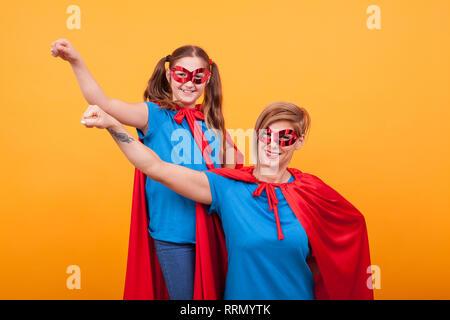 Little girl dressed like superhero standing alongside the