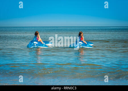 two little girls are swimming on pumped dolphins in the sea in summer - Stock Photo