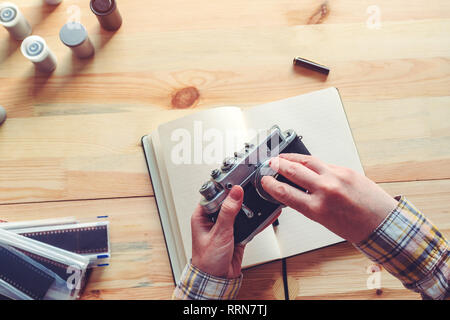 Photographer changing lens on vintage film photography camera in studio, selective focus - Stock Photo