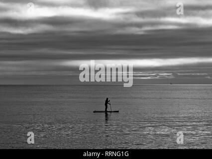 Paddle boarder alone at sea - Stock Photo
