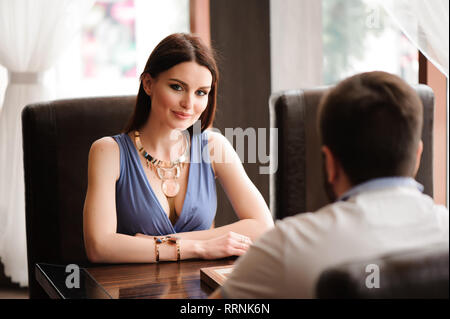 Young couple playing chess in the restaurant - Stock Photo