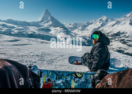 Personal perspective snowboarders on snowy ski slope, Zermatt, Switzerland - Stock Photo