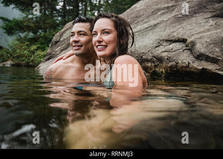 Affectionate young couple swimming in lake - Stock Photo