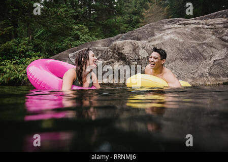 Happy young couple floating in inflatable rings on lake - Stock Photo