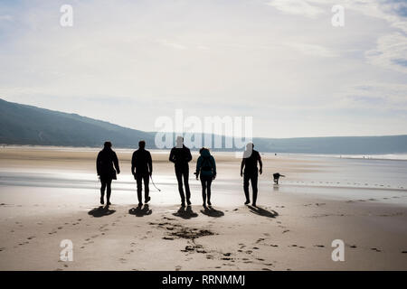 A group of people walking on a quiet sandy beach at low tide. Woolacombe, North Devon, England, UK, Britain - Stock Photo