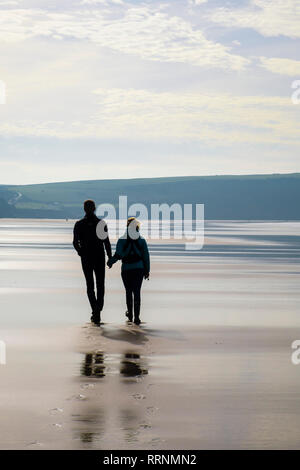 A couple holding hands walking on a quiet sandy beach at low tide. Woolacombe, North Devon, England, UK, Britain - Stock Photo