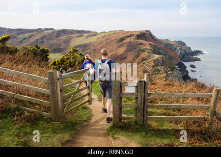 Two people walking on the South West Coast Path and Tarka Trail towards Bull Point from Lee Bay, Ilfracombe, North Devon, England, UK, Britain - Stock Photo