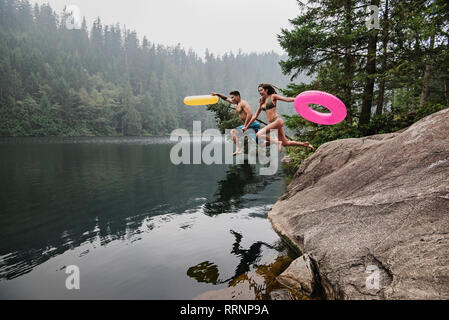 Playful young couple with inflatable rings jumping into remote lake, Squamish, British Columbia, Canada - Stock Photo