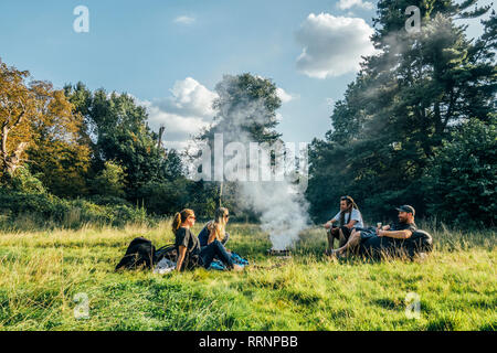 Friends camping, relaxing around campfire in remote field - Stock Photo