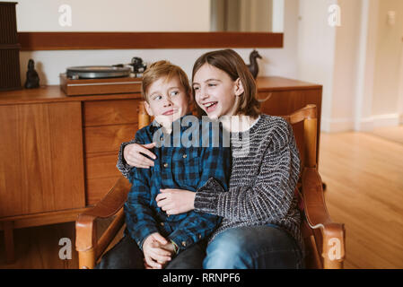 Portrait laughing sister hugging brother making a face - Stock Photo