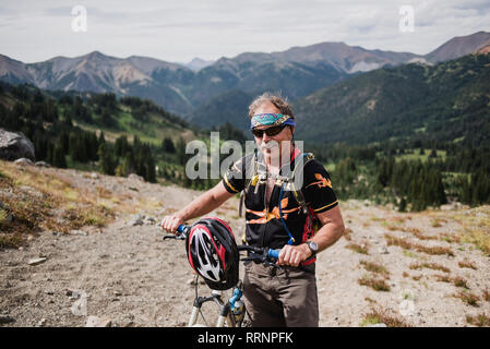 Portrait active senior man mountain biking in remote landscape, Chilcotin Mountains, British Columbia, Canada - Stock Photo